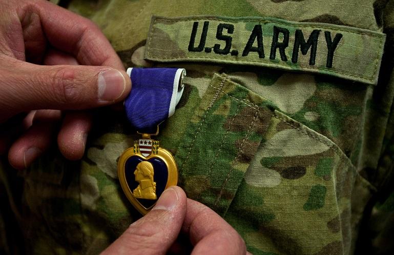 Un ufficiale appunta la Purple Heart sull'uniforme di un soldato ferito in combattimento