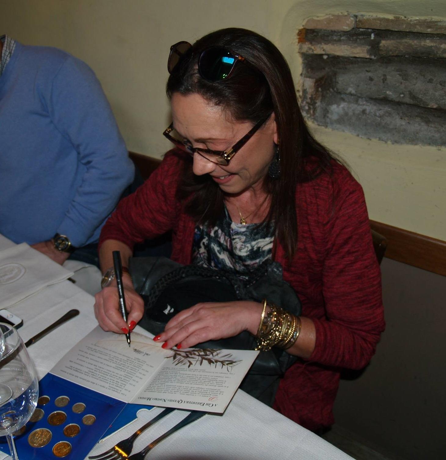 Loredana Pancotto autografa una delle sue divisionali realizzate per San Marino ad un incontro con alcuni appassionati collezionisti