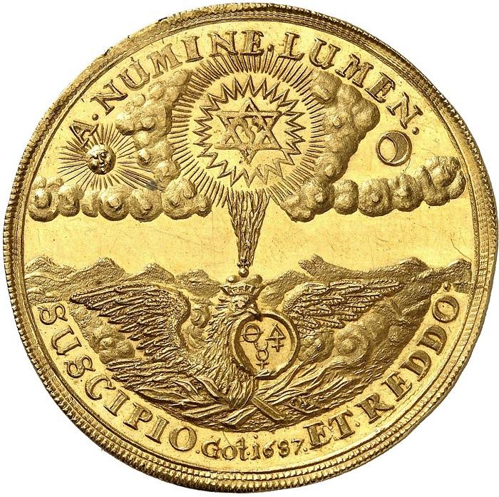 """Il tallero dell'alchimista, rovescio: A NUMINE LUMEN SUSCIPIO ET REDDO (""""Da Dio ho ricevuto la luce e la restituisco""""), in esergo Got[ha] 1687. Sopra un banco di nuvole, tra il sole (l'oro) e la luna (l'argento) l'esagramma (l'unificazione di tutti gli elementi e la pietra filosofale), che reindirizza i suoi raggi concentratisull'aquila alchemica (processo di vaporizzazione); l'aquila tiene nel becco un """"uroboros"""" (simbolo di eternità e di materia prima, i prodotti di partenza) è il suo becco che intreccia i simboli alchemici di sale, zolfo e mercurio"""