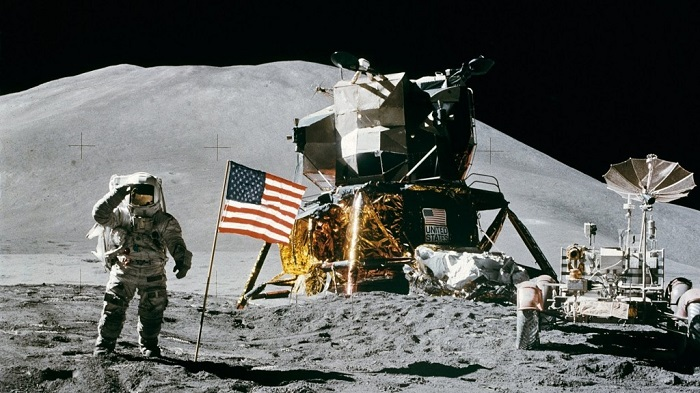 Una delle foto scattate sulla Luna: si vedono chiaramente l'astronauta con la bandiera USA, il modulo lunare e il rover usato per la perlustrazione del terreno
