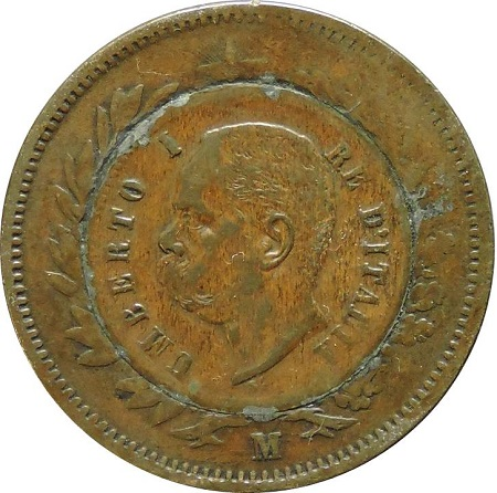 """""""La moneta dei tre re"""", il rovescio: Umberto I campeggia su un tondello da 2 centesimi saldato al centro del campo del curioso manufatto numismatico"""