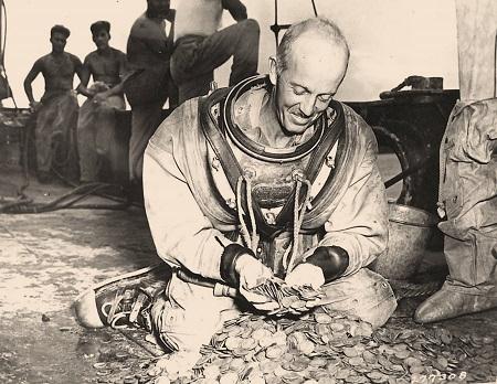 Appena finita la guerra si procede al recupero del tesoro di Manila: in quest'immagine d'epoca un palombaro della US Navy sorride di fronte ad una montagna di monete d'argento