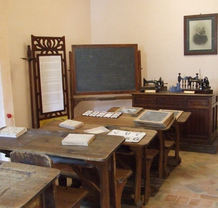 """Aula """"Metodo Montessori"""" ricostruita con materiali originali a Città di Castello: in alto il ritratto del barone Leopoldo Franchetti che, con la giovane moglie Alice, finanziò la Montessori"""