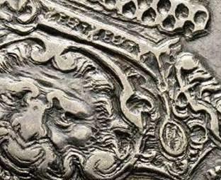 La finezza di questa rarissima moneta spicca nello spallaccio con protome leonina dell'armatura e nel collare dell'Annunziata, di cui si distinguono i decori FERT e il pendente