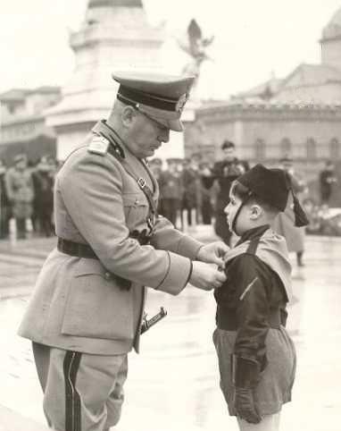 Benito Mussolini, di fronte all'Altare della Patria, premia un giovanissimo balilla durante una cerimonia