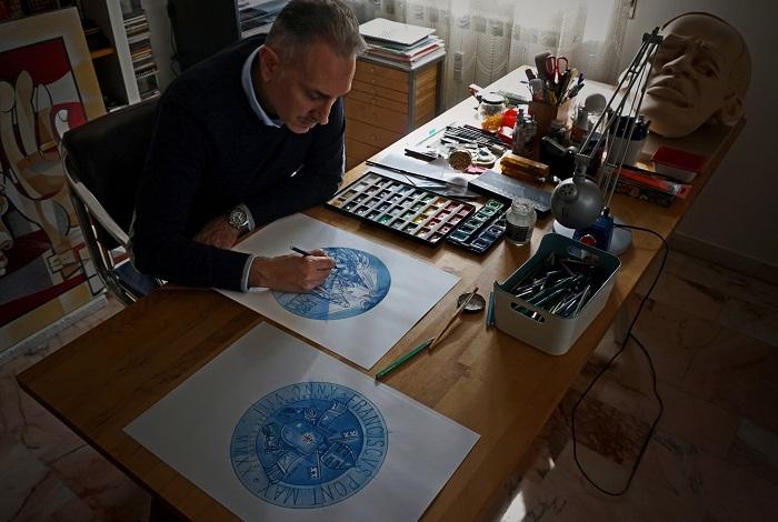 L'artista al lavoro sui disegni preparatori da cui è nata la nuova moneta di papa Francesco in emissione il 10 dicembre