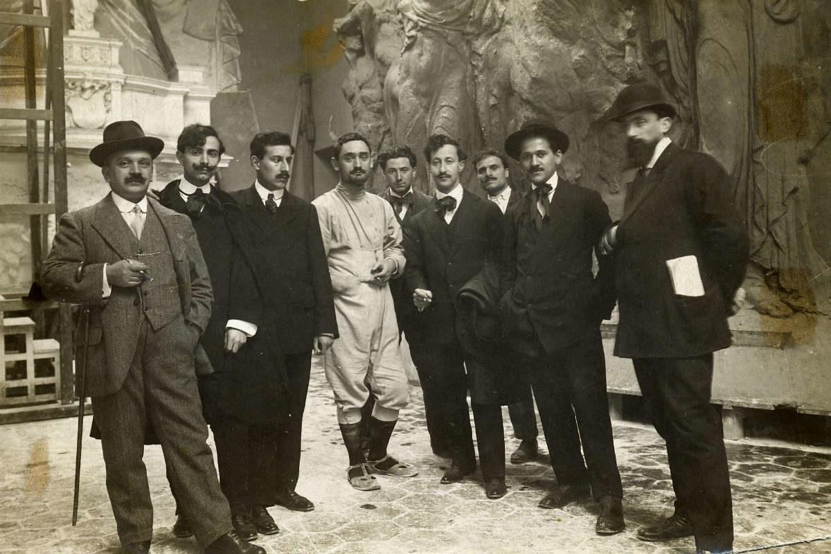 """Lo scultore bresciano Angelo Zanelli (al centro, in tuta chiara da lavoro) con alcuni """"visitatori"""" del grande cantiere nel quale furono realizzate le monumnetali sculture che ancora oggi ornano il Vittoriano"""