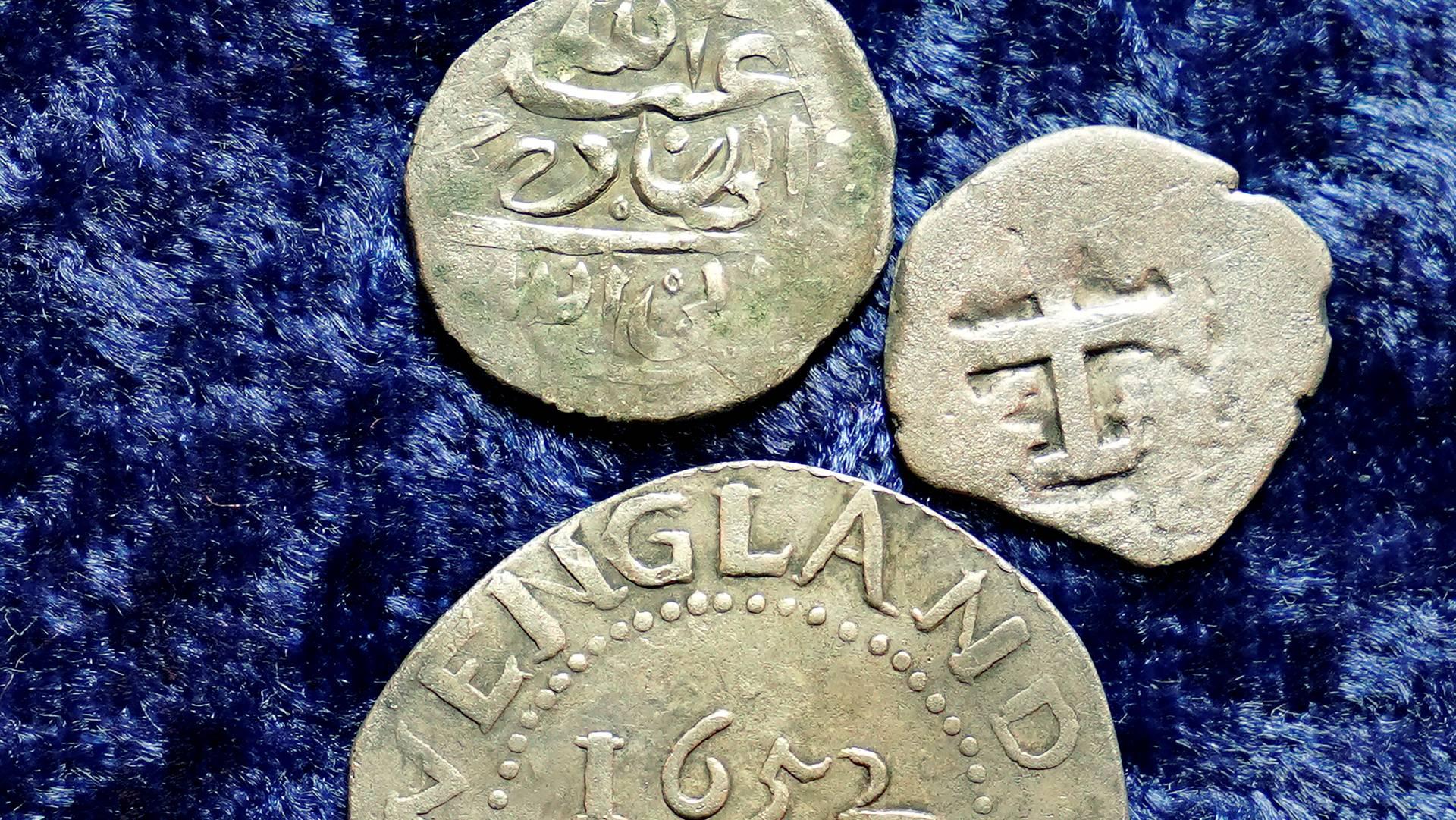 Alcuni dei reperti numismatici probabilmente legati al pirata Every: una moneta yemenita in argento, uno spicciolo spagnolo in rame e un gettone del New England