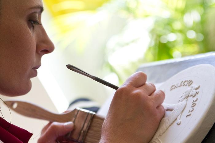 La fase di rifinitura del gesso, delicato passaggio in cui la creatività artistica va coniugata con la perizia tecnica nella lavorazione del materiale creatore: il soggetto prende forma, il gol è vicino!