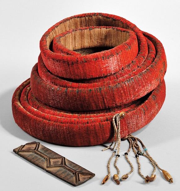 Moneta naturale formata da spirali in legno ricoperte di piume di volatile e decorate con fili di perline e conchiglie