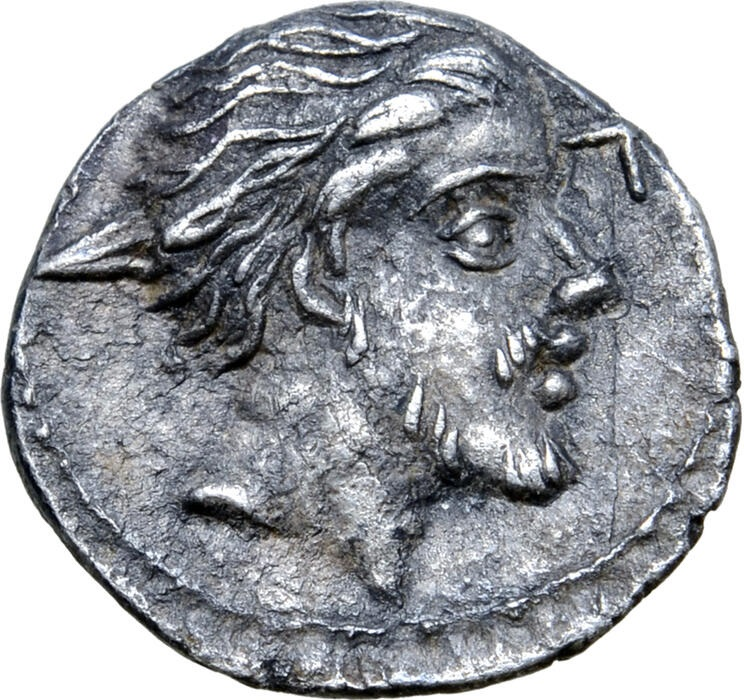Al dritto del sesterzio d'argento, un profilo di guerriero gallico la cui testa è trafitta (?) da un'arma appuntita e ripiegata